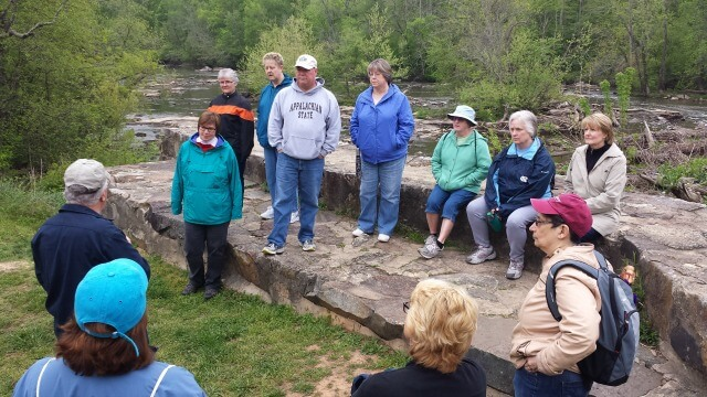 photo of a group of hikers sitting and standing at the Glencoe Dam listening to guest trail guide Bob Ellis sharing history of the Glencoe Mill