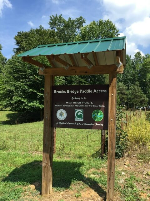 photo of the welcome kiosk at Brooks Bridge Paddle Access a wooden structure with a green peaked roof and a sign, trees in the background
