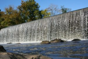 photo of the Haw River rushing over the Glencoe Dam on a sunny day with blue sky and trees in the background and river with rocks in foreground