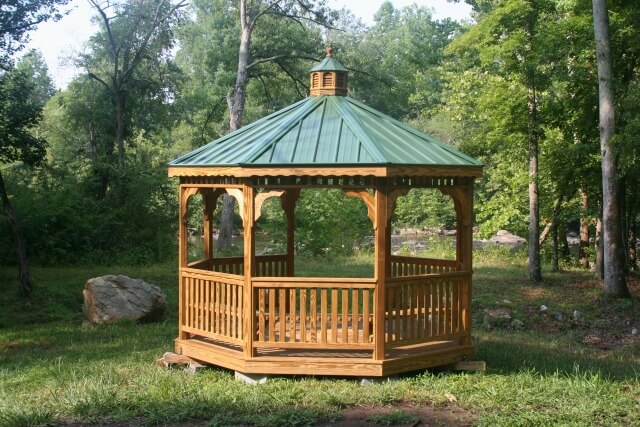 photo of an octagonal wooden gazebo with a green roof in a field with the river and trees in the background