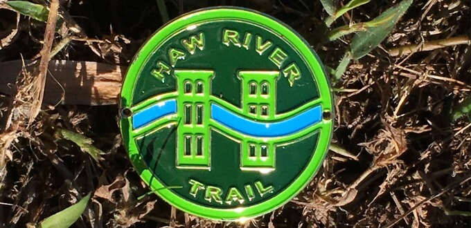 photo of the metal and enamel hiking stick medallion designed as the Haw River Trail logo