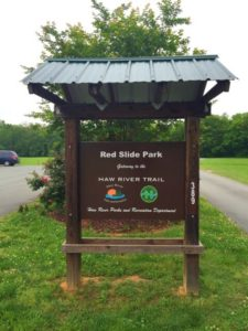 photo of the welcome sign at Red Slide Park with a tree and the parking area behind it