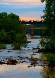 a view of the river from Red Slide Park at sunset with train cars on the traintrack bridge over the river