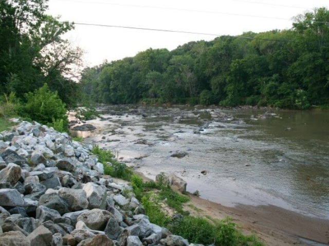 photo of the river with rocks in the river and a pile of rocks on the left foreground