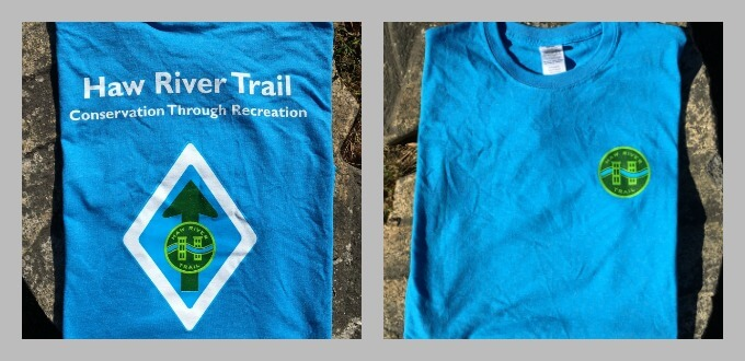 photo of back of blue HRT t shirt reads Haw River Trail, Conservation through Recreation, with the HRT trailblaze of a diamond with an arrow and the logo and underneath it says blazing trails since 2000, front of shirt has small HRT logo on left chest
