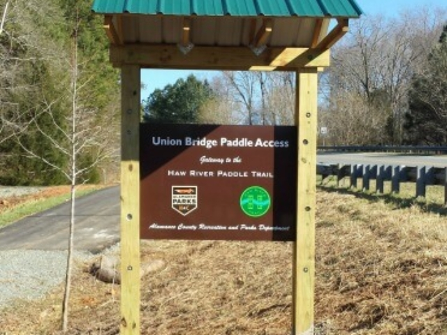 photo of the welcome kiosk at Union Bridge Paddle Access which has a brown sign and green roof set into a wood frame