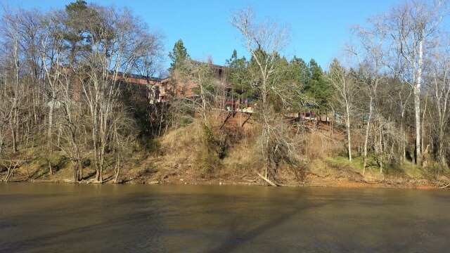 photo looking across the calm Haw River from Saxapahaw Island up to the Rivermill buildings