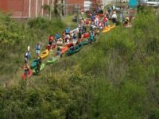 phoot of a hollside with kayakers and their boats lined up and waiting to get on the river