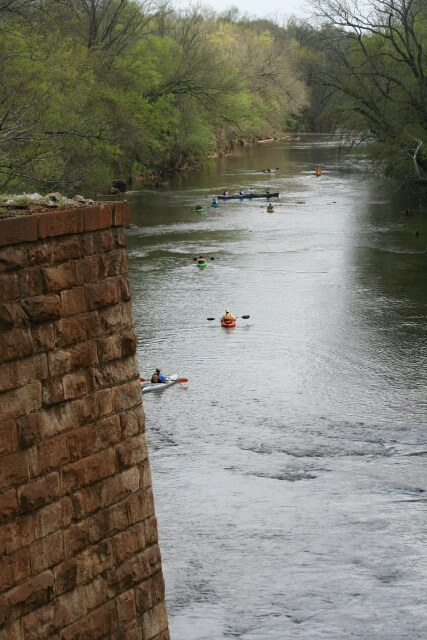 photo of a line of paddlers on the river with a brick bridge piling in the foreground and trees in the background